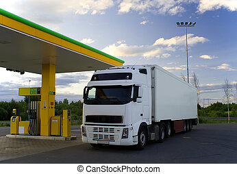 Truck at a fuel-station - White truck is at a fuel station.
