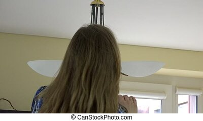 housewife woman changing light bulbs. Back view. - housewife...