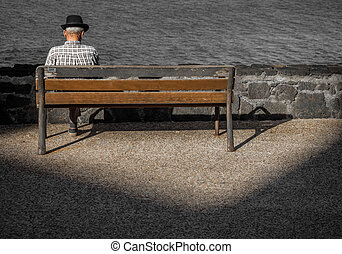 Old man sitting on a wooden bench