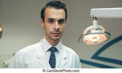 Dentist at the dental clinic - Handsome dentist man at the...