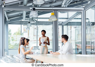 Young business people discussing financial report in...