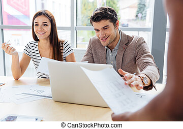 Smiling woman and man discussing project in the office -...