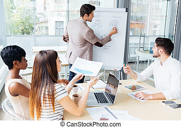 Business team creating presentation using flipchart in...