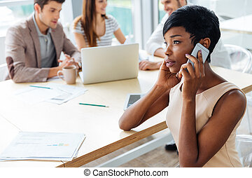 Businesswoman sitting and talking on mobile phone in office...