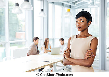 Confident african businesswoman standing with arms crossed...