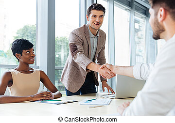Happy business people shaking hands in office