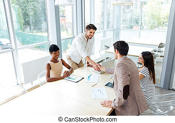Businessmen shaking hands on business meeting in office -...