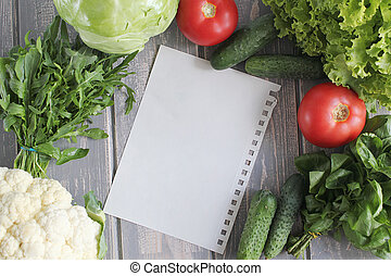 Sheet and composition of vegetables on grey wooden desk....