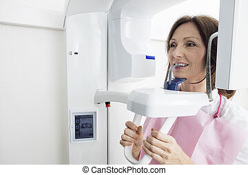Patient Using Digital Panoramic Xray Machine While Looking...