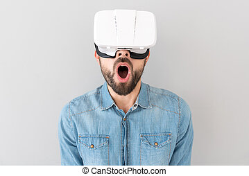 Surprised bearded man using virtual reality device - Full of...