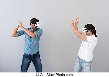 Serious involved men using virtual reality glasses -...