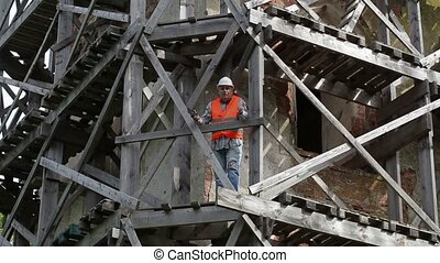 Angry construction worker standing on wooden scaffolding and...