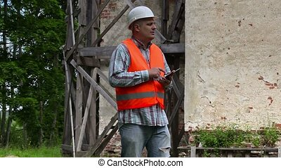 Construction worker thinking and using tablet PC
