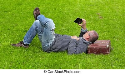 Man with suitcase sleeping on grass and take pictures on...