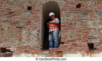 Construction worker using tablet PC and checking old wall