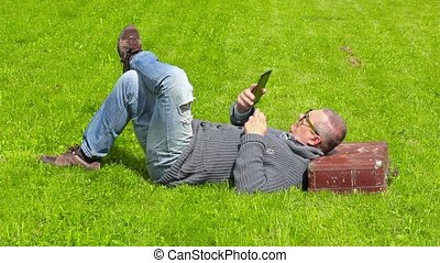Man with suitcase sleeping on grass and using tablet PC