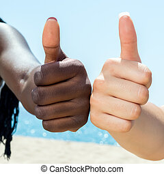 Macro close up of diversity hands doing thumbs up.