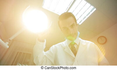 Dentist holding dental lamp and tools - Low angle portrait...
