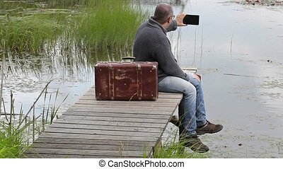 Man with suitcase sitting near lake and take pictures