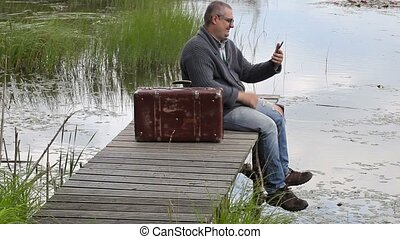 Man with suitcase sitting near lake and talking on phone