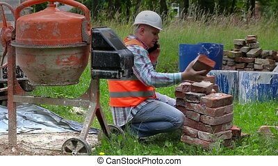 Construction worker checking old bricks and talking on smart...