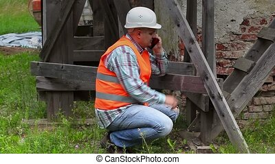 Construction worker checking wooden scaffolding and talking...
