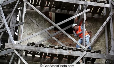 Construction worker walking on wooden scaffolding and...