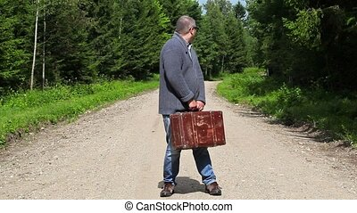 Man with suitcase on rural road in forest