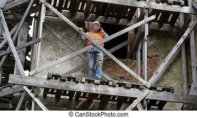 Construction worker standing on scaffold - Construction...