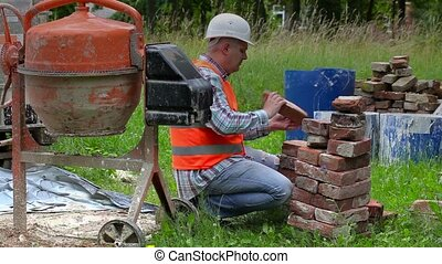 Construction worker sorting old bricks near concrete mixer