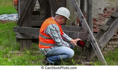 Construction worker checking wooden scaffolding and take...