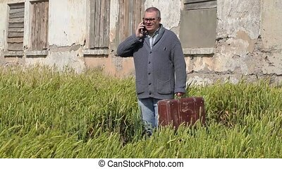 Man on field with suitcase talking on phone