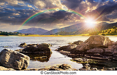 lake with boulders in mountains at sunset - composite...