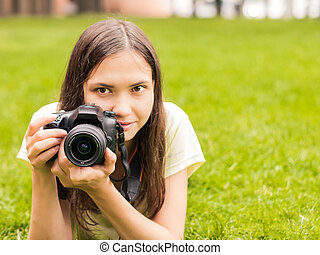 girl with camera lie down on grass - Young woman...