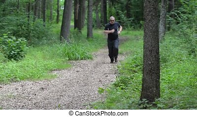 Tired runner on forest trail near tree
