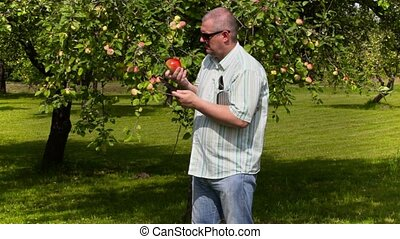 Gardener examine apple and writes in tablet PC