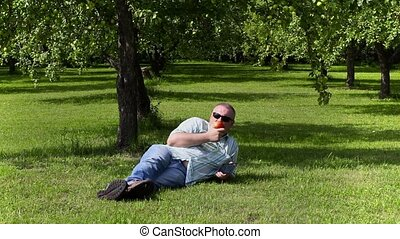 Man eating an apple lying in apple orchard