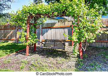 Hanging swing at fenced back yard with nice landscape desing...
