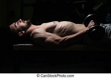 Man In The Gym Exercising Forearm With Dumbbells - Young...