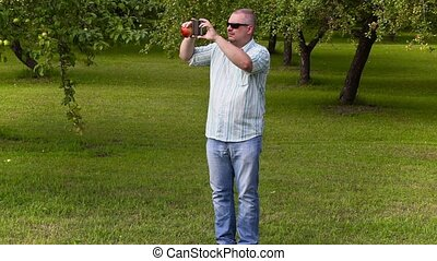 Gardener take pictures and walking in apple orchard