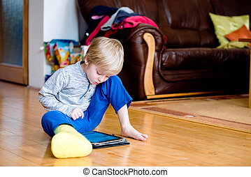 Boy with broken leg in cast playing on tablet - Cute little...