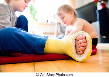 Boy with broken leg with his brother playing - Close up of...