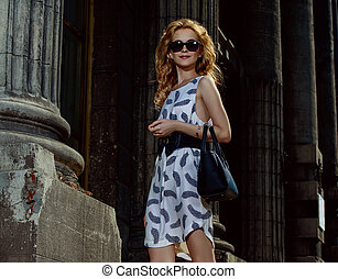 walking street - Happy young woman walking in the city on a...
