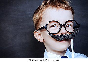 play a role - Funny little boy in fathers glasses plays with...