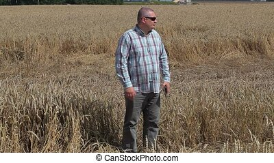 Worried farmer on destroyed cereal field