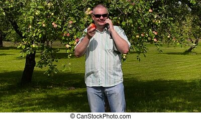 Gardener with apple and smart phone in apple orchard