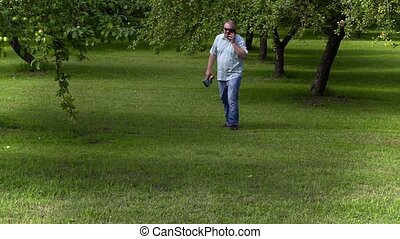 Gardener walking and talking on phone in apple orchard