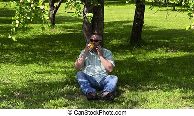 Man smelling an apple and talking on the phone