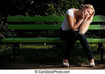 sad young woman sitting on bench in park - beautiful sad...