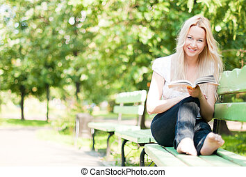 young woman reading book in park - young woman sitting on...